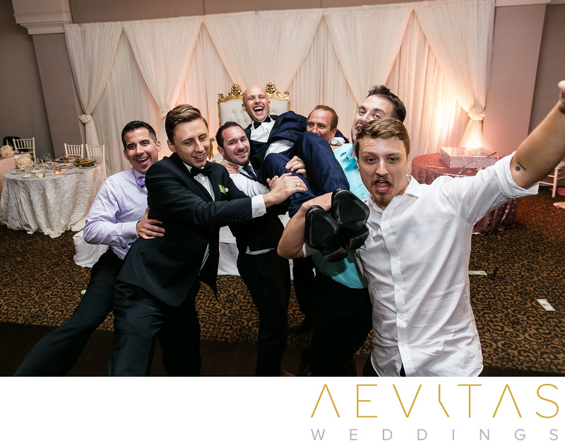 Men lift groom at Sacramento ballroom reception