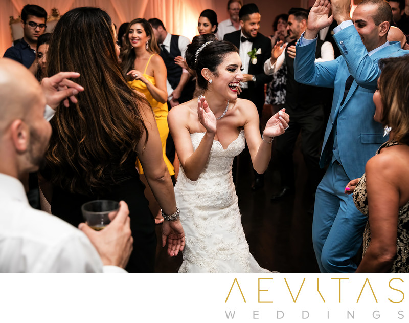 Bride surrounded by wedding guests on dance floor