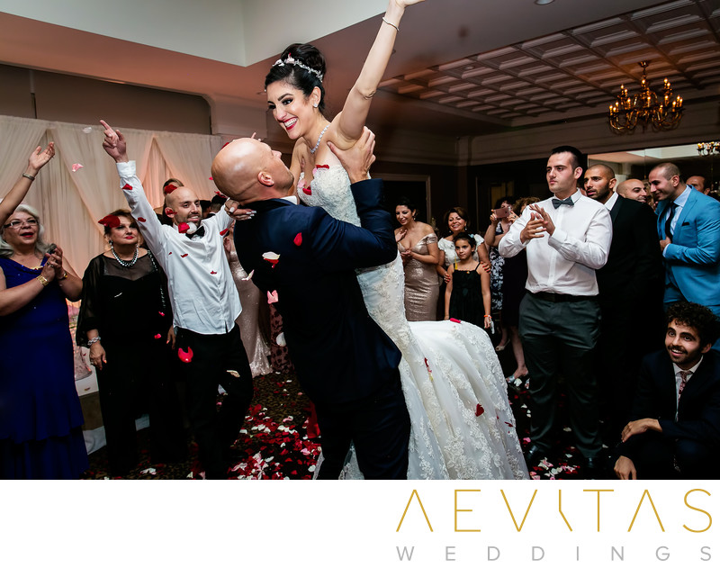 Groom lifts bride during Persian flower dance
