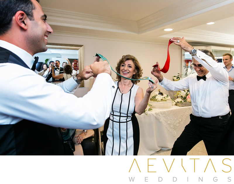 Groom dancing with parents and Armenian colors