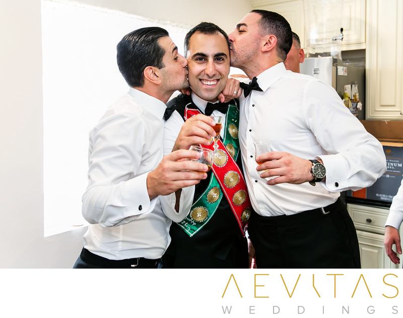Groomsmen kiss groom at Armenian wedding party