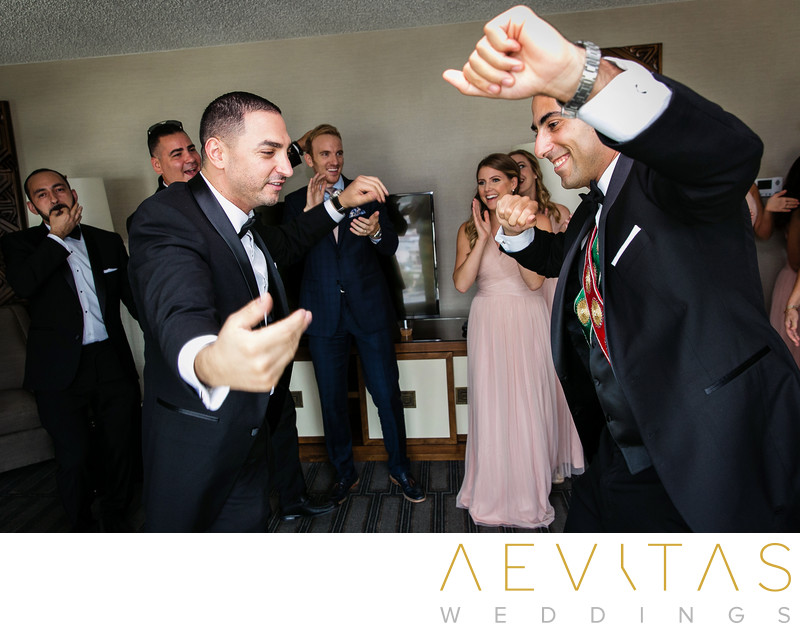 Groom dancing with friend at Armenian wedding party