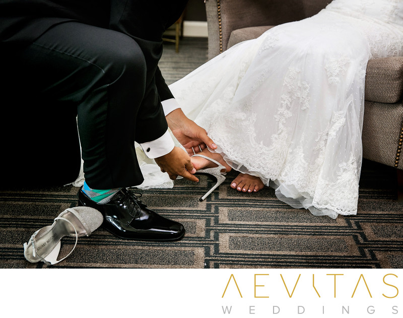 Close-up of brother putting on bride's shoes at wedding