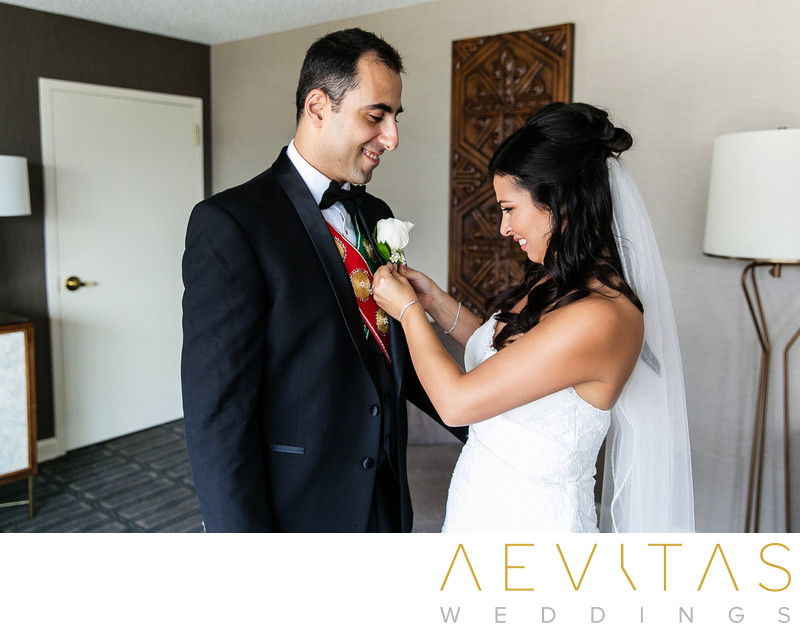 Bride fixes groom's boutonniere at Glendale wedding