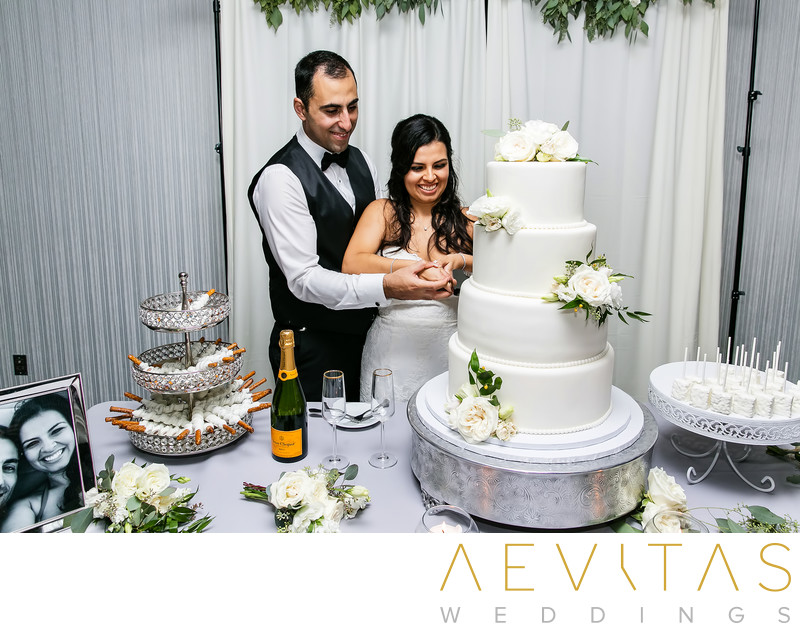 Couple cut multi-tiered cake at Glendale wedding