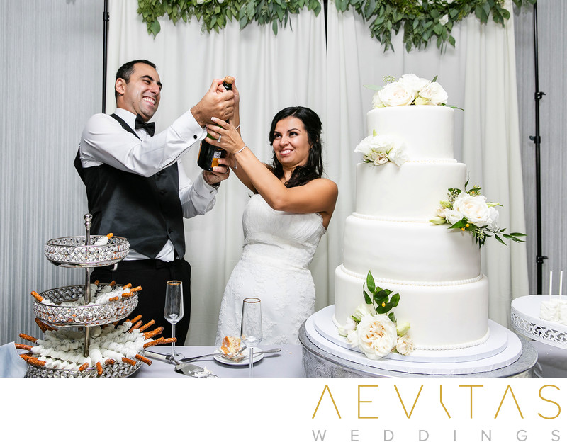 Couple pop champagne with wedding cake in Glendale