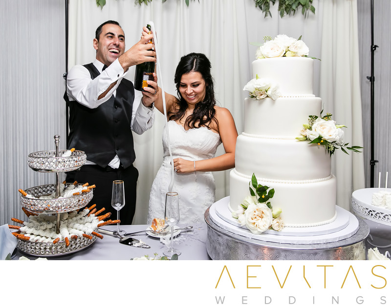 Couple with champagne flowing at cake cutting ceremony