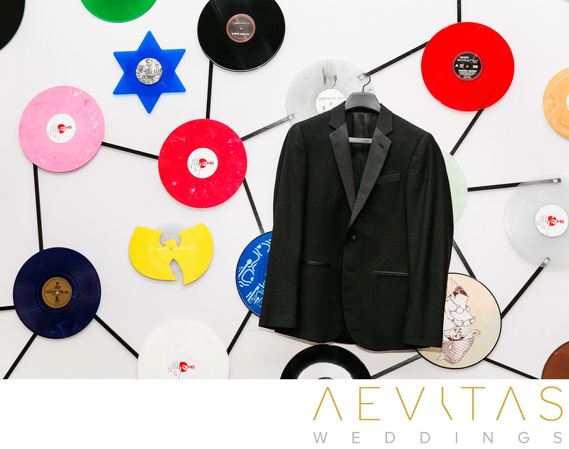 Groom's suit jacket with records on wall behind