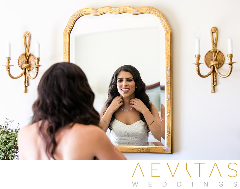 Reflective photo bride getting ready in ornate mirror