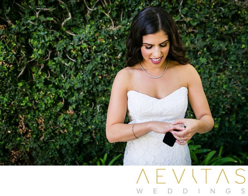 Bride trying on ring in front of hedge at Skirball, LA