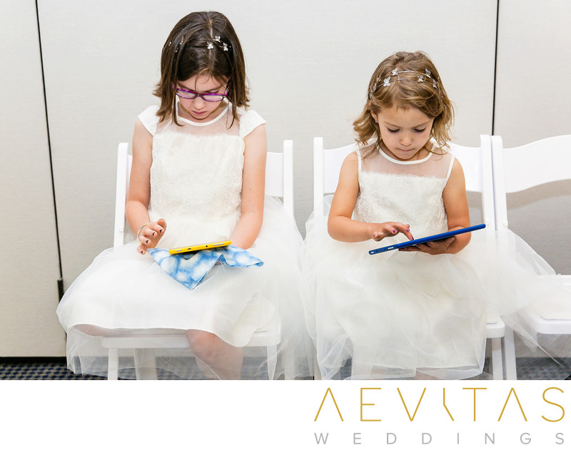 Flower girls playing on tablets at Los Angeles wedding
