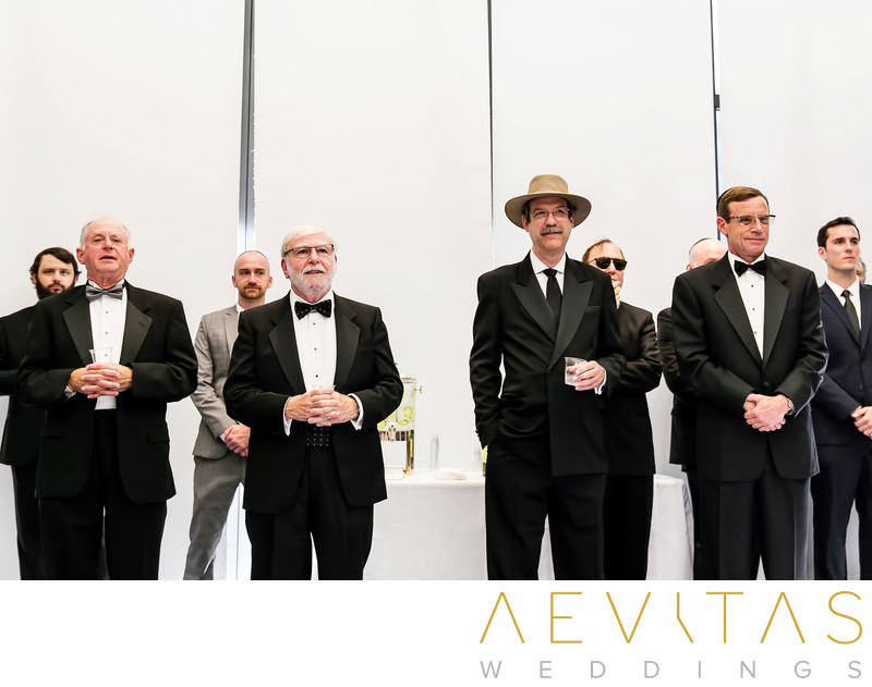Men standing with drinks at Jewish Tish ceremony