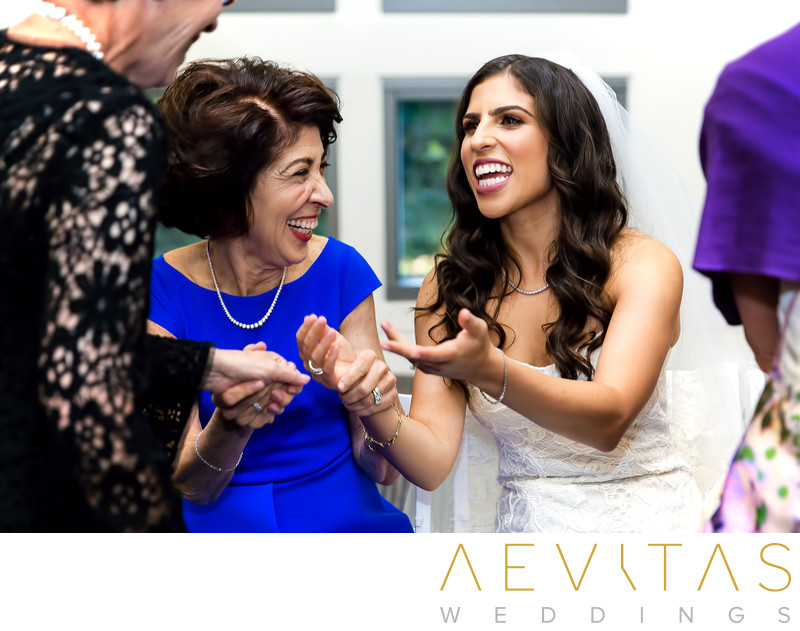 Bride laughing with mom and guest at Jewish Bedeken