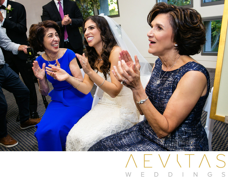 Bride and moms clapping at Jewish Bedeken ceremony