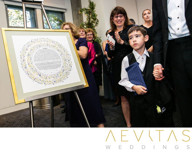 Young guest with Ketubah at Jewish wedding in LA