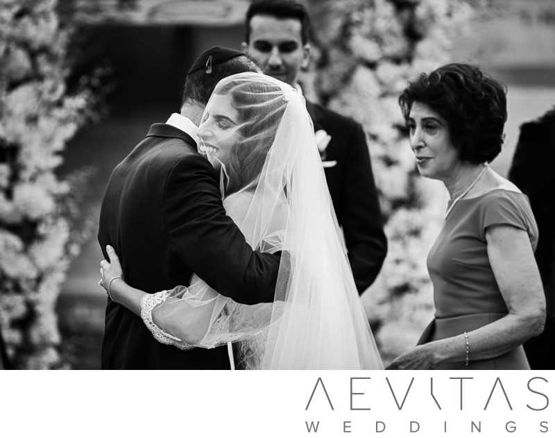 Black and white photo bride hugging parents at Skirball