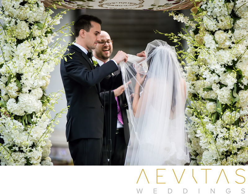 Groom lifts bride's veil beneath Chuppah Jewish wedding