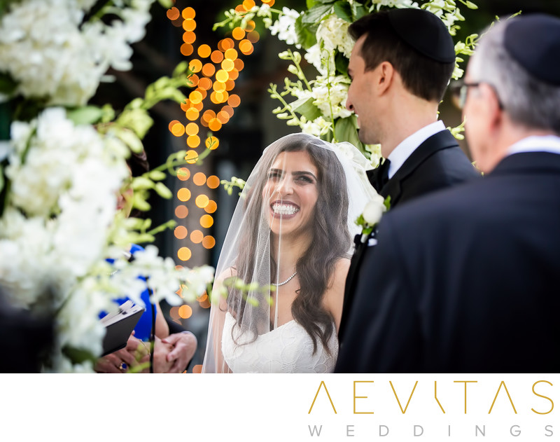 Bride smiling at groom with flowers at LA wedding