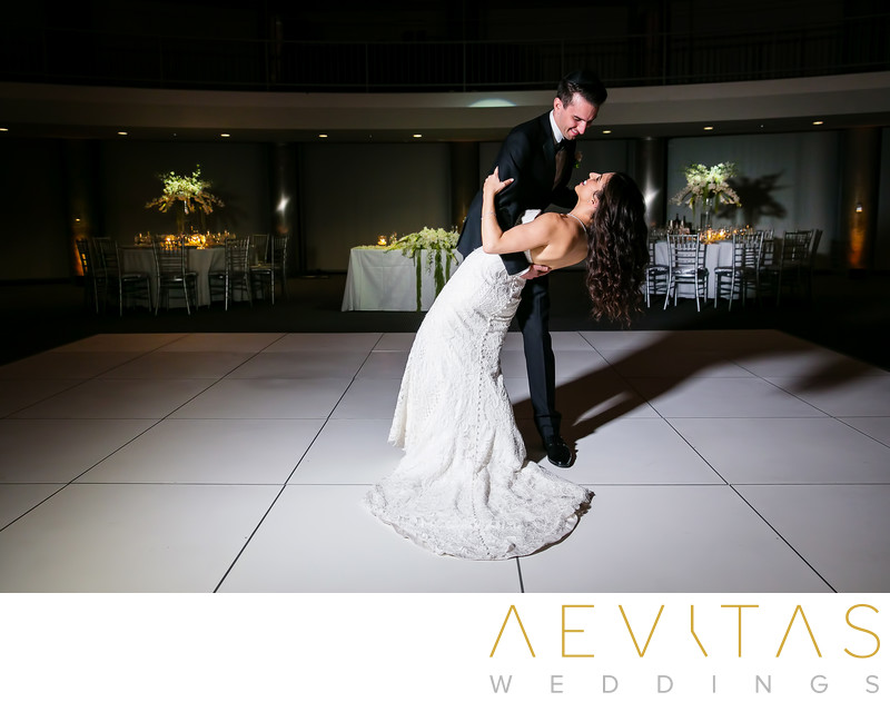 Groom dips bride on Skirball ballroom dance floor