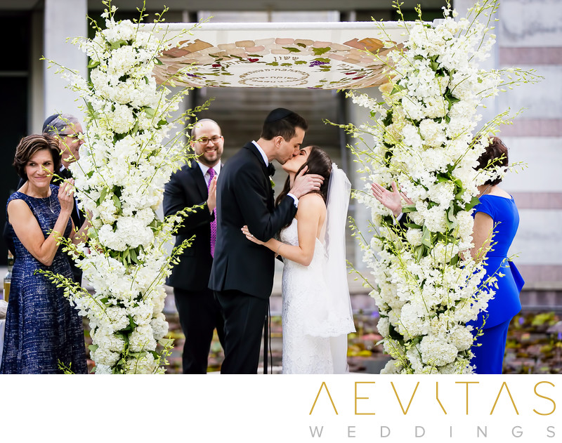Couple kiss beneath Chuppah at Jewish wedding in LA
