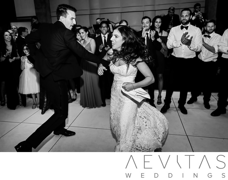 Black and white couple spinning at Jewish reception