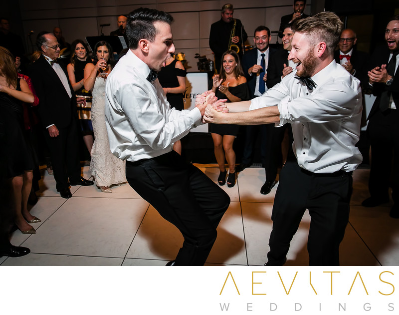 Groom and best man spinning at Jewish wedding party