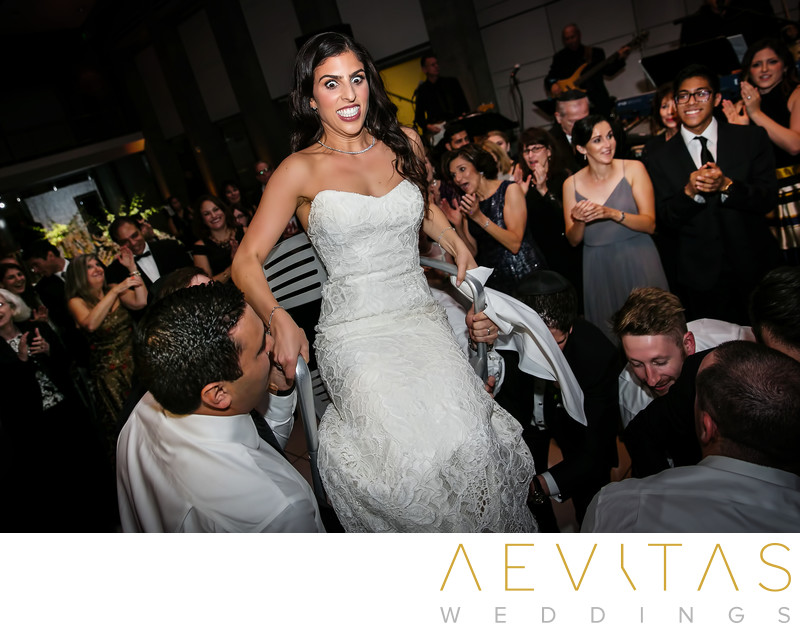 Bride reaction Horah chair dance at Jewish wedding