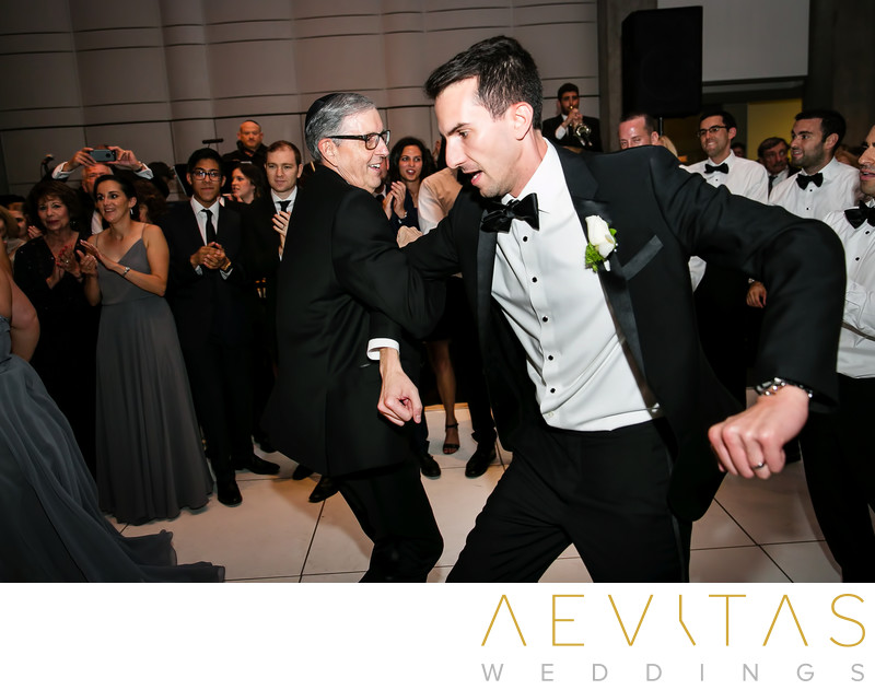Groom and father dancing at Jewish wedding reception