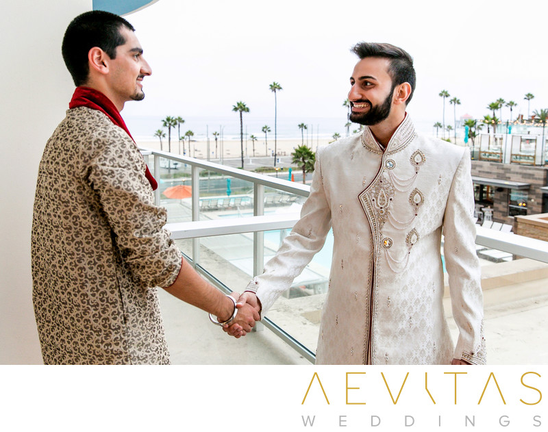 Groom shakes hand with groomsman at Pasea Hotel and Spa