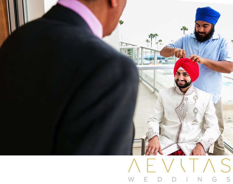 Tying turban on groom with father in foreground