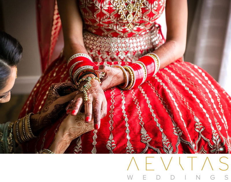 Creative photo of Indian bride's hands and red sari
