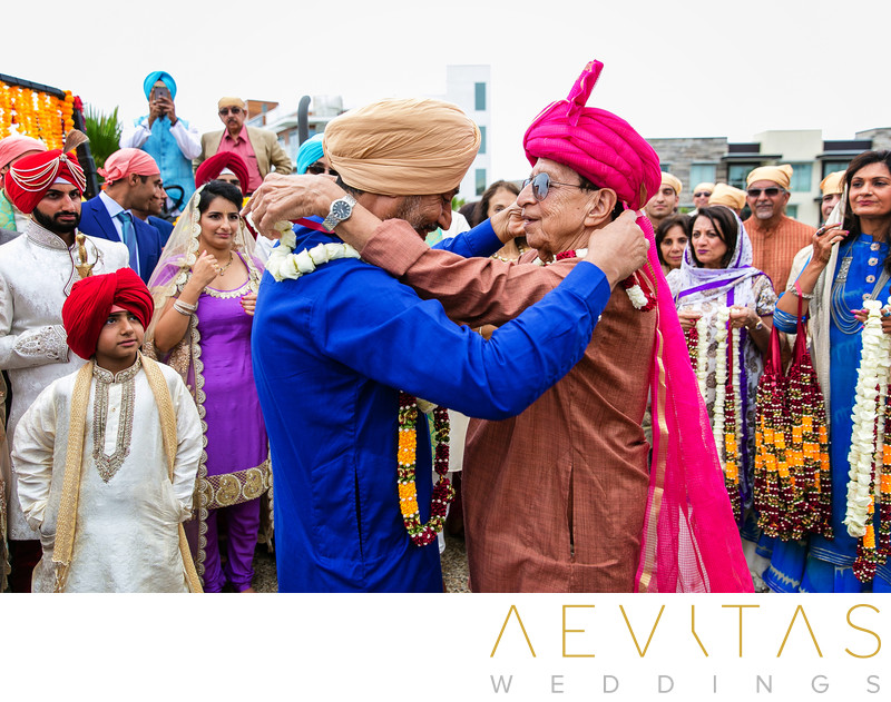 Men exchange garlands at Sikh wedding ceremony