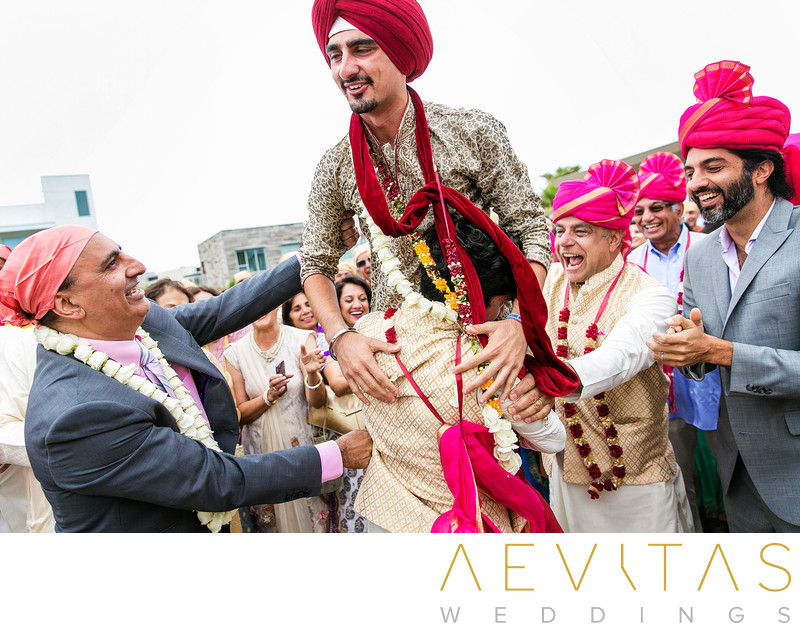 Man in red turban lifted during Indian wedding game