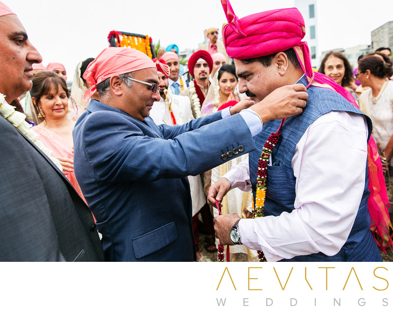 Man puts garland around neck at Indian wedding
