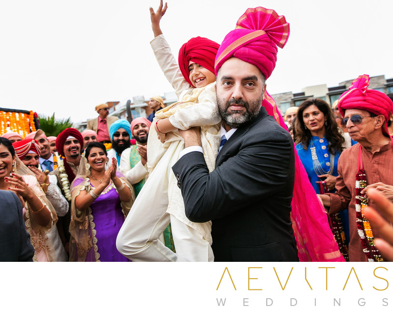 Man lifts young boy at Indian Baraat ceremony