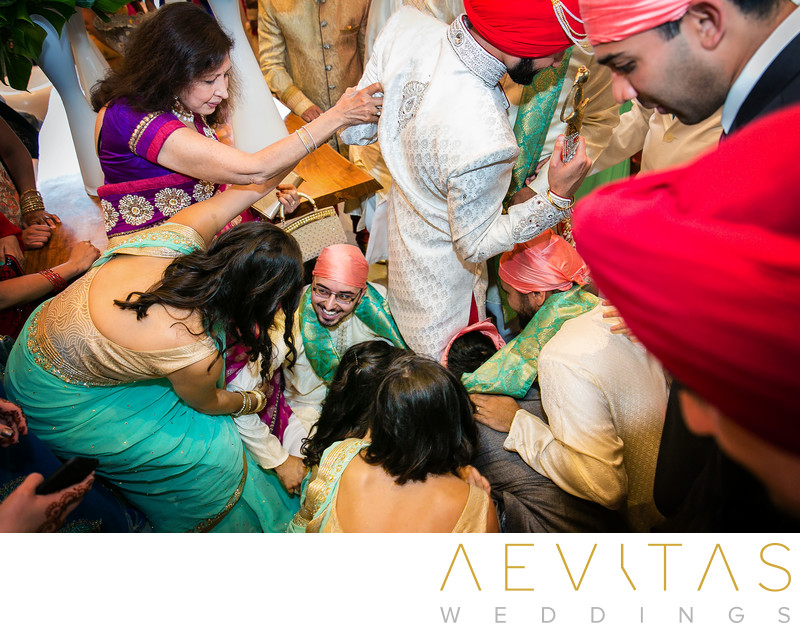 Guests reach for groom's shoes in Indian wedding game