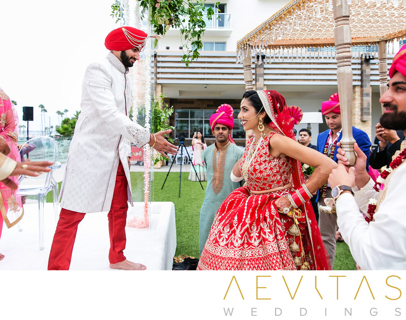 Groom receives bride at garden Indian wedding ceremony