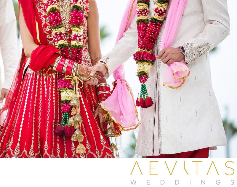 Close-up couple holding hands at Hindu wedding ceremony