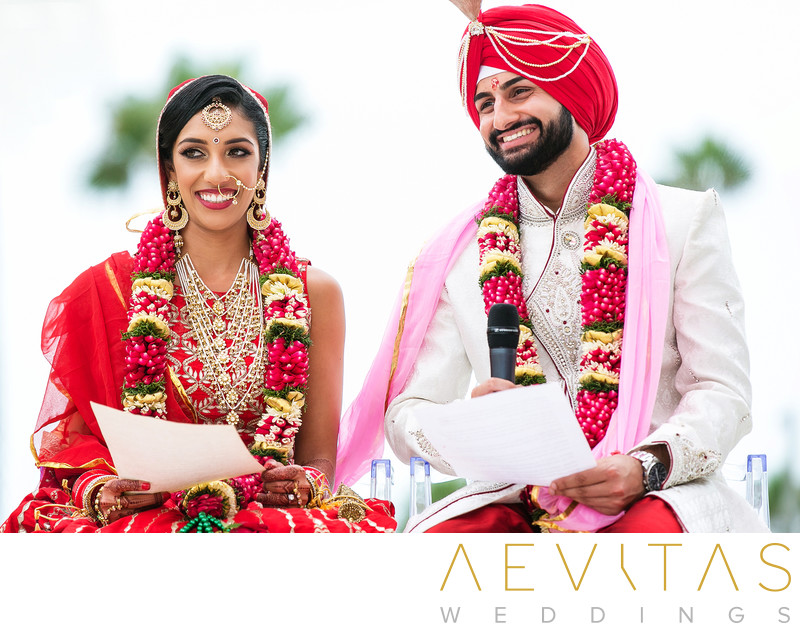 Bride and groom smile with vows at Indian wedding