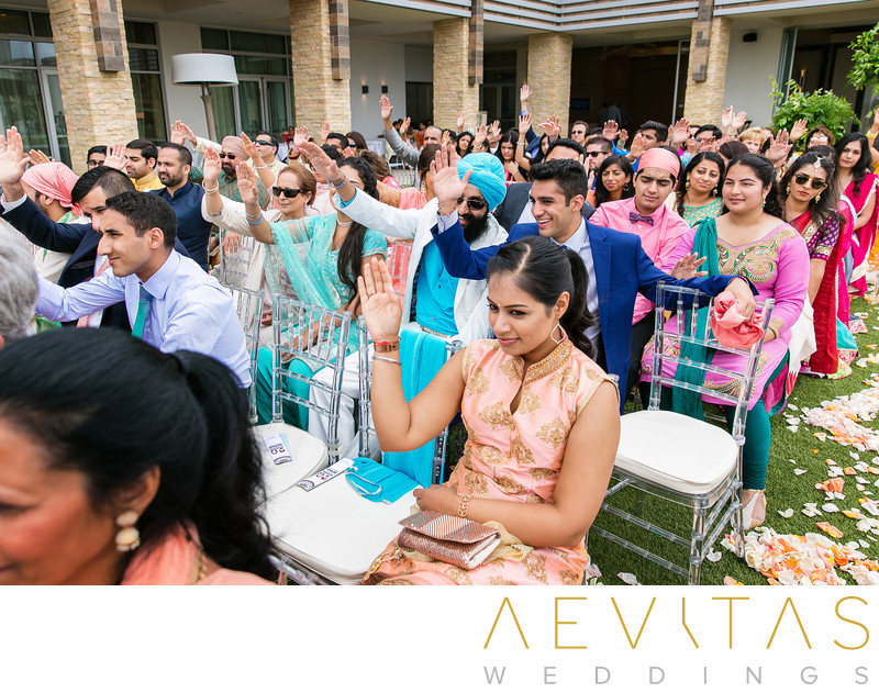 Wedding guests put hands in air at Hindu ceremony