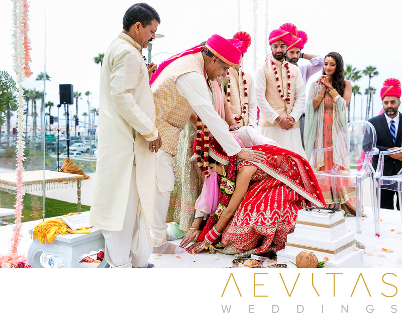 Bride touches father's feet at Hindu wedding ceremony
