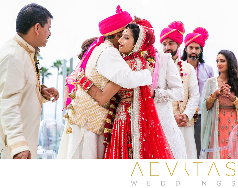 Bride embraces father at Hindu wedding ceremony