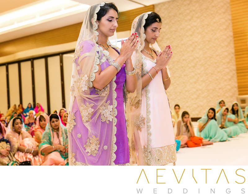Sisters pray at Pasea Hotel Sikh wedding ceremony