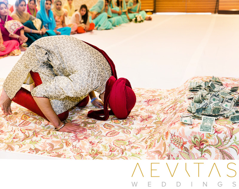 Man bows in front of money at Sikh wedding ceremony