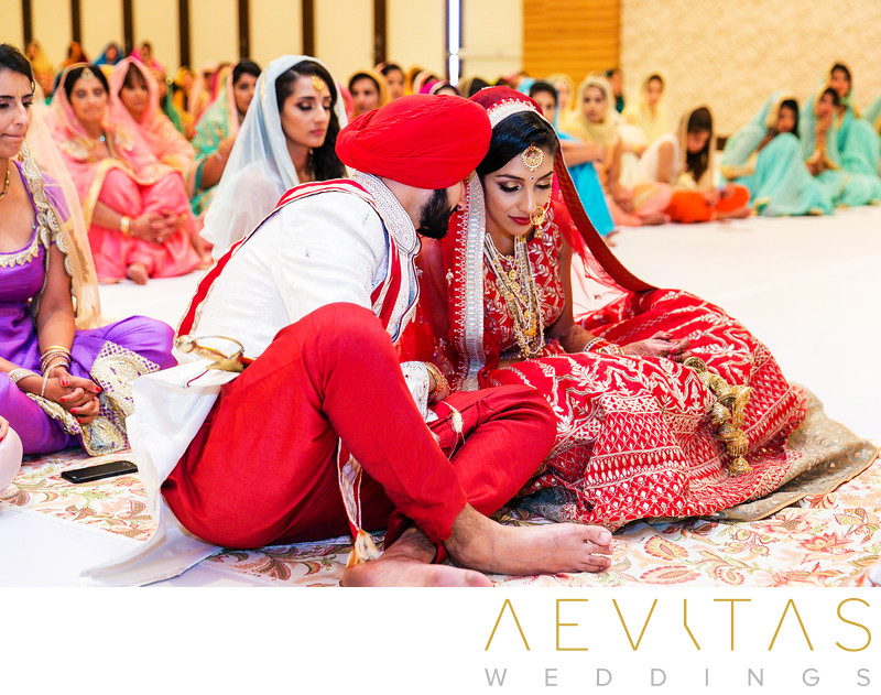 Groom whispering to bride at Sikh wedding ceremony