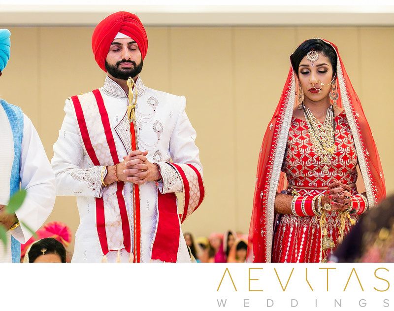 Bride and groom pray at Sikh wedding ceremony