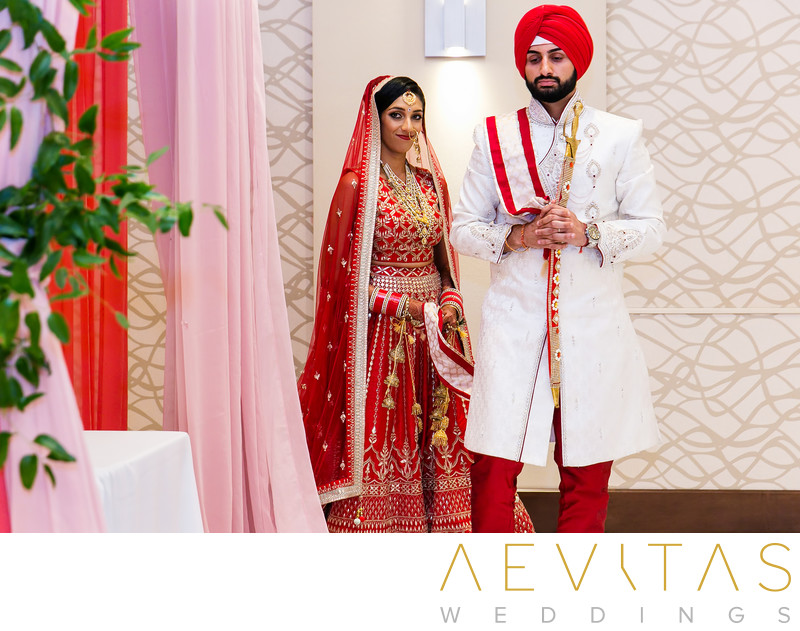 Couple walk around stage at Sikh wedding ceremony