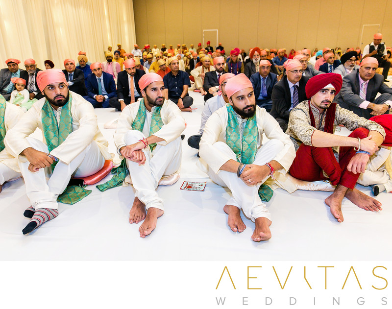 Men with head coverings seated at Sikh wedding ceremony