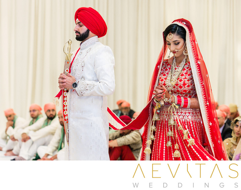 Bride and groom praying at Sikh wedding ceremony