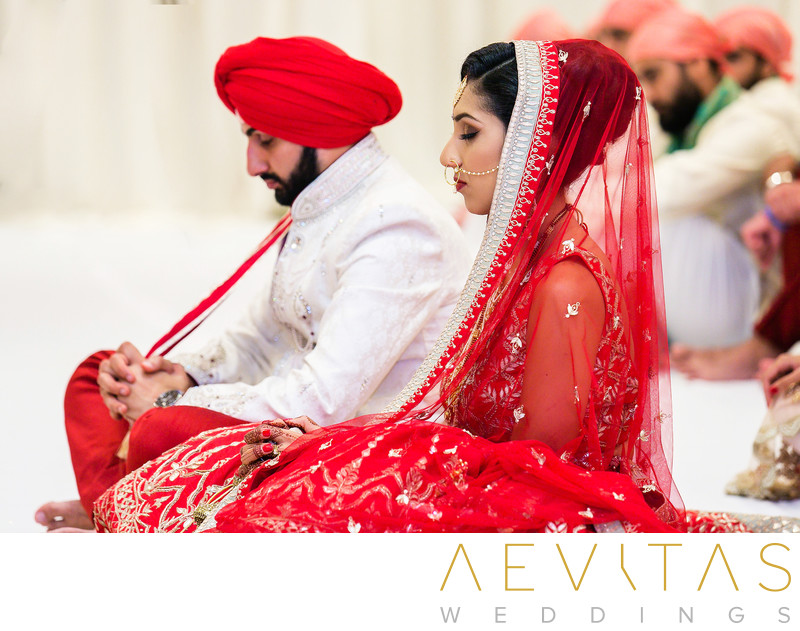 Bride and groom with eyes closed at Sikh wedding
